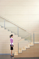 Businesswoman Standing at bottom of stairway