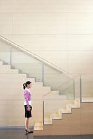 Businesswoman Standing at bottom of stairway