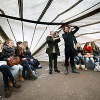 Nederland, Amsterdam , 1 november 2011..Discussie met scholieren en lieden van de Amsterdamse Occupy beweging in de z.g. circustent van het Occupy campement op het Beursplein worden dagelijks diverse cursussen gegeven en debatten gevoerd..Jonathan Duijn (r) student geschiedenis en theaterwetenschappen en Roy Brussé voormalig Maagdenhuis activist leggen scholieren uit hoe je in  een debat d.m.v. gebaren zaken duidelijk kunt maken.Foto:Jean-Pierre Jans