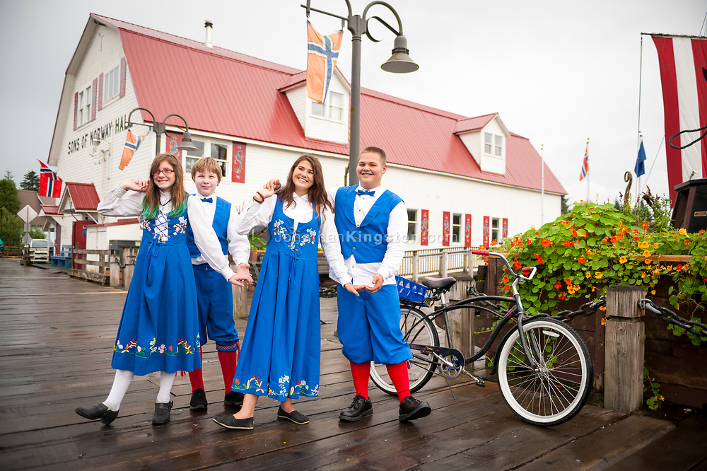 Young teenagers wearing blue, white and red Norwegian clothing stand holding hands in front of the Sons of Norway hall in Petersburg, Alaska.