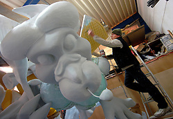 """AALST, BELGIUM - FEB-1-2007 - Dmitri Cornand, of the Krejeis team, works on a float for the Carnival of Aalst. The carnival of Aalst, celebrated every year in February, is one of the oldest and most famous in Flanders. It is locally called Vastenavond (Mardi Gras). During the carnival, thousands of people, most of them masked, dance in the streets of the city. The carnival is announced in the beginning of January with the Magi's Festival; a few weeks later, the Prince of the carnival is elected. On carnival's Saturday, the Mayor of the city gives full power to the Prince, who rules the city for the rest of the carnival. On Sunday afternoon, some 70 masked and costumed groups, all from Aalst, parade through the city on elaborate floats. The floats and the masks change every year as they reflect current events and take weeks to prepare. The parade is led by a pair of giants that represent the town and the """"Ros Balatum"""" (the Balatum horse). The cortege parades again on Monday after the Onion Throwing ceremony. On Tuesday, Mardi Gras (by tradition, the day before Ash Wednesday), is known as the day of the 'Voil Jeannetten' (literally: """"the Dirty Jennies""""),  where men dressed like big-breasted women holding ludicrous objects entertain the crowd. In the evening, the carnival mannequin is burned on the Great Square and official order is restored to the city.(PHOTO  © JOCK FISTICK)"""
