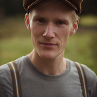 Close portrait of young man wearing a flat cap outdoors looking straight forward