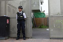 © Licensed to London News Pictures. 04/06/2017. LONDON, UK.  A police officer stands outside the police cordon as scaffolding is erected around a ground floor flat at a block of flats in Kings Road, Barking where police arrested several people today in connection with the London Bridge terror attack. Photo credit: Vickie Flores/LNP