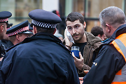 London, UK. 14 October, 2019. Police officers speak to a climate activist from Extinction Rebellion who was assaulted by a man in King William Street on the eighth day of International Rebellion protests across London. Today's activities were concentrated around the  City of London's finance district.