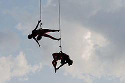 Two aerialists perform acrobatics hanging suspended, against the evening sky, from the Strawberry Mansion Bridge during the 2015 Invisible River Festival on the Schuylkill River on Saturday. (Bastiaan Slabbers/for PhillyVoice)