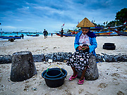 03 AUGUST 2017 - KUTA, BALI, INDONESIA: A woman waits to buy fish from fishermen returning from the ocean on Jimbrana Beach in Kuta. The beach is close to the airport and a short drive from other beaches in southeast Bali. Jimbrana was originally a fishing village with a busy local market. About 25 years ago, developers started building restaurants and hotels along the beach and land prices are rising. The new emphasis on tourism is changing the nature of the area but the fishermen are still busy very early in the morning.     PHOTO BY JACK KURTZ