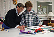 Donna Meeks and Kae Schmickley (from left) both of Cedar Rapids cut out fabric for quilted envelopes for adoption papers as St. Luke's volunteers work at the Hiawatha Care Center in Hiawatha on Thursday October 15, 2009.