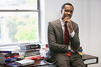 Portrait of a confident African American businessman sitting on office desk