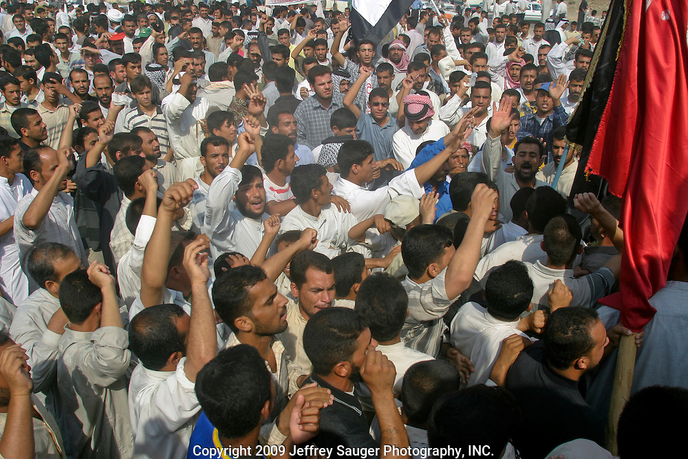 Protestors rally before marching to the City Council Building in Nassiriyah, Iraq, Monday, August 11, 2003. Approximately 3000 peaceful protestors marched on the building, where Coalition Provencial Authority instilled city council members were holed up, demanding they resign and the citizens have the right to elect their own leaders. Heavily armed Italian troops guarded the buiding as Italian helicopters flew overhead. After several hours of negotiations, the protestors said they would not leave until the resignations were complete. Apparently by the end of the day, the resignations finally came.