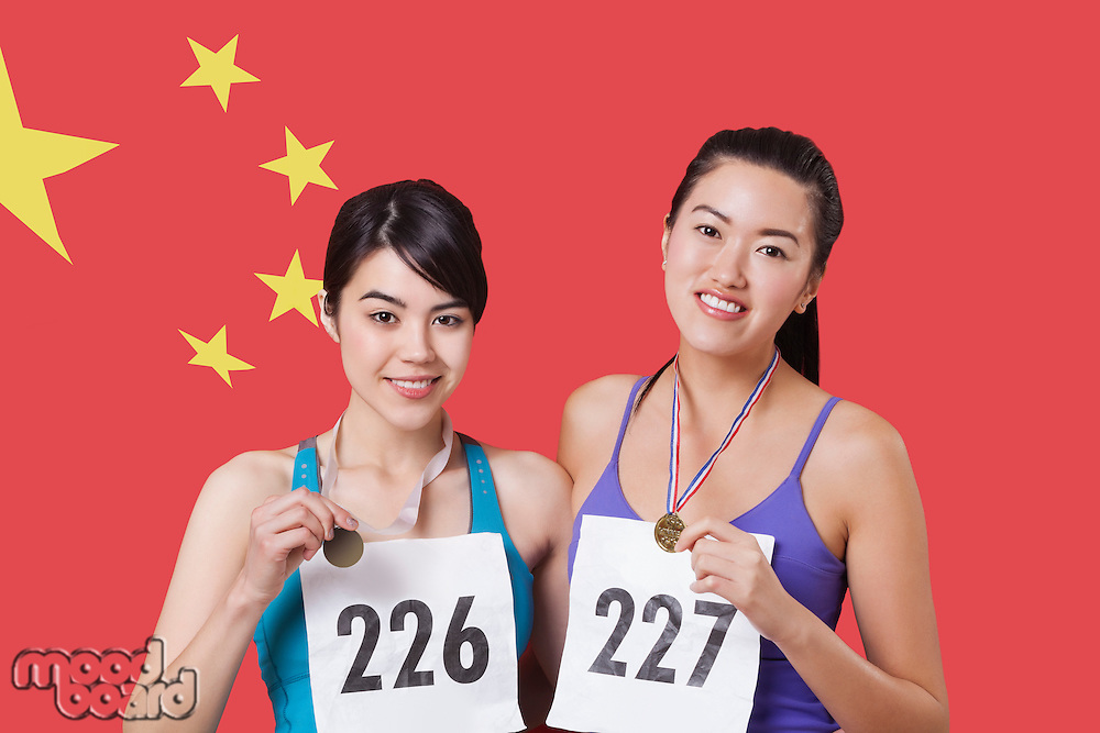 Portrait of smiling young medalists standing against Chinese flag