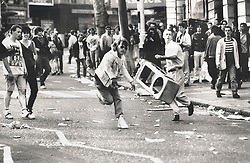 © Licensed to London News Pictures. 25/03/2020. London, UK. In this image from March 31st 1990 a protester throws a traffic bollard towards police advancing up Charing Cross Road during the London poll tax riots. The protest on the last day of March in 1990 started peacefully when thousands gathered in a south London park to demonstrate against Margaret Thatcher's Government's introduction of the Community Charge - commonly known as the poll tax. Marchers walked to Whitehall and Trafalgar Square where violence broke out with the trouble spreading up through Charring Cross Road and on to the West End. Police estimated that 200,000 people had joined the protest and 339 were arrested. The hated tax was eventually replaced by the Council Tax under John Major's government in 1992.  Photo credit: Peter Macdiarmid/LNP