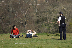 © Licensed to London News Pictures. 09/04/2020. London, UK. A police officer speaks to two people sat on the grass in Greenwich Park. The government has asked that people continue to remain indoors over the Easter Weekend. Photo credit: Rob Pinney/LNP