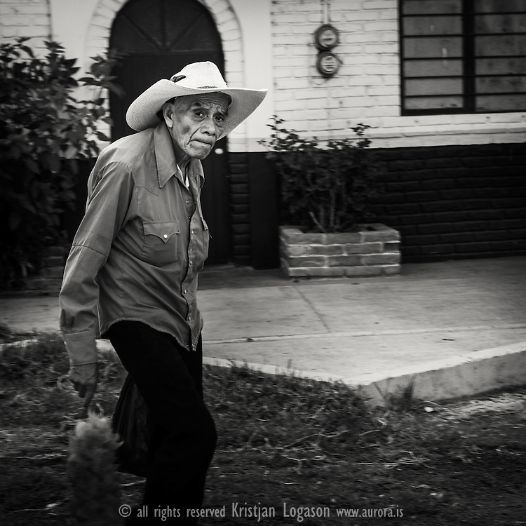 Old man wearing a blue shirt with red brush in his hand walking in Pazcuaro