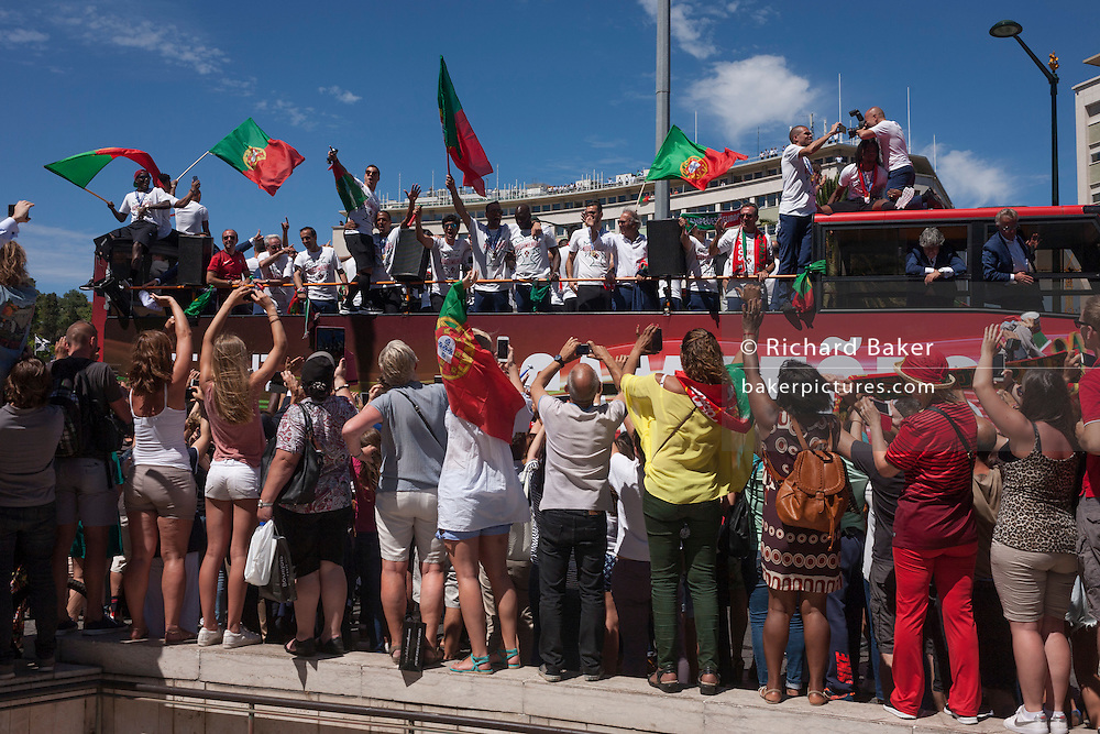 Thousands of Portuguese sports fans cheer their national football team bus as it passes-by during their victory procession through the capital's streets, the day after the Euro 2016 final with France, on 11th July 2016, in Lisbon, Portugal. Waving flags and voicing their love for the team in Praca Marques de Pombal in the largely corporate and banking district of the city, they take photos and cheer their favourite players, including the national hero/deity, Christiano Ronaldo. (Photo by Richard Baker / In Pictures via Getty Images)