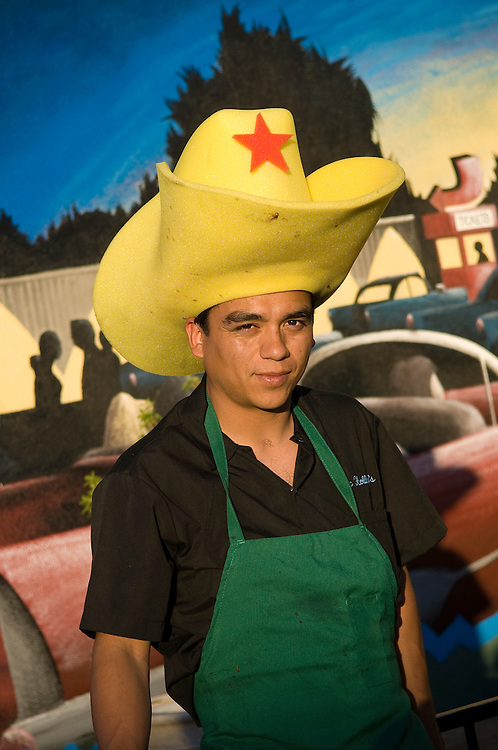BBQ chef for Doc Holliday's Steakhouse wearing giant foam cowboy hat; Williams, Arizona.