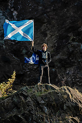 October 6, 2018 - Edinburgh, Lothian, United Kingdom - A man is seen holding 2 Scottish flags whilst standing on a mountain...Thousands of Scottish independence supporters marched through Edinburgh as part of the 'all under one banner' protest, as the coalition aims to run such event until Scotland is 'freeâ (Credit Image: © Stewart Kirby/SOPA Images via ZUMA Wire)
