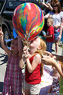 Emma Brown, 7, of Williamstown, enjoys her balloon during the Fourth of July Parade in Waterbury on Saturday