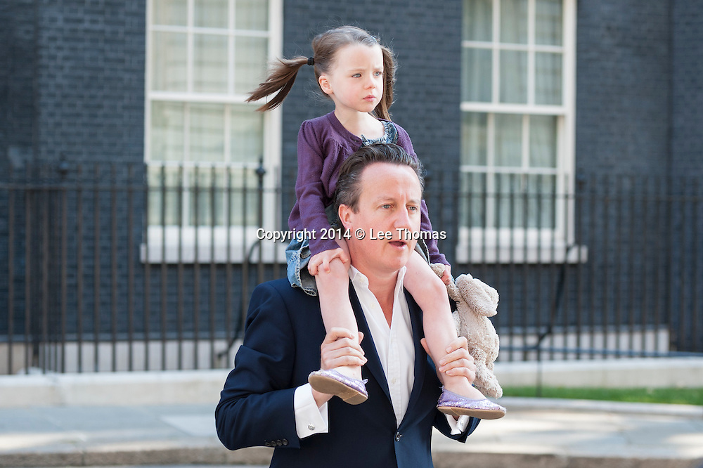 Downing Street, London, UK. 1st July 2014. PM David Cameron carries his daughter Florence on his shoulders as he walks out of Number 10 Downing Street prior to a Cabinet Meeting.