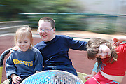 three children on a merry-go-round with motion blur background