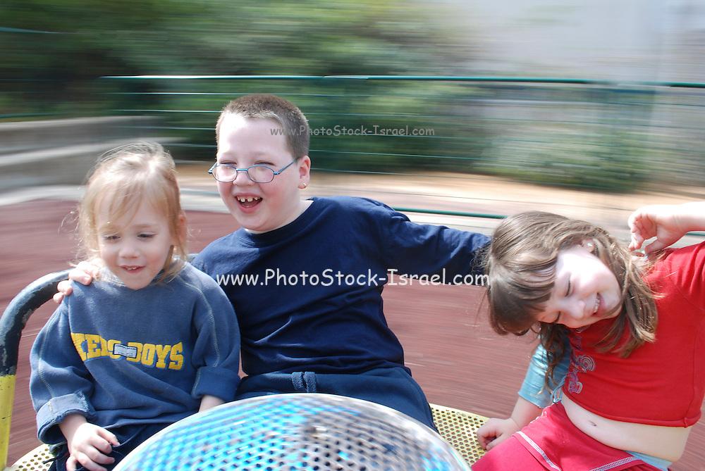 three children on a merry-go-round with motion blur background