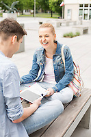 Smiling young woman with male friend studying on bench at college campus