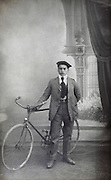 studio portrait of a young adult male posing with bicycle