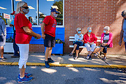 "03 AUGUST 2020 - JEWELL, IOWA:  Residents of Jewell wait for the Jewell Market to open Monday morning. The only grocery store in Jewell, a small community in central Iowa, closed in 2019. It served four communities within a 20 mile radius of Jewell. Some of the town's residents created a cooperative to reopen the store. They sold shares to the co-op and  held fundraisers through the spring. Organizers raised about $225,000 and bought the store, which had its ""soft opening"" July 8. The store celebrated its official reopening Monday August 3. Before the reopening, Jewell had been a ""food desert"" for seven months. The USDA defines rural food deserts as having at least 500 people in a census tract living 10 miles from a large grocery store or supermarket. There is a convenience store in Jewell, but it sells mostly heavily processed, unhealthy snack foods that are high in fat, sugar, and salt.        PHOTO BY JACK KURTZ"