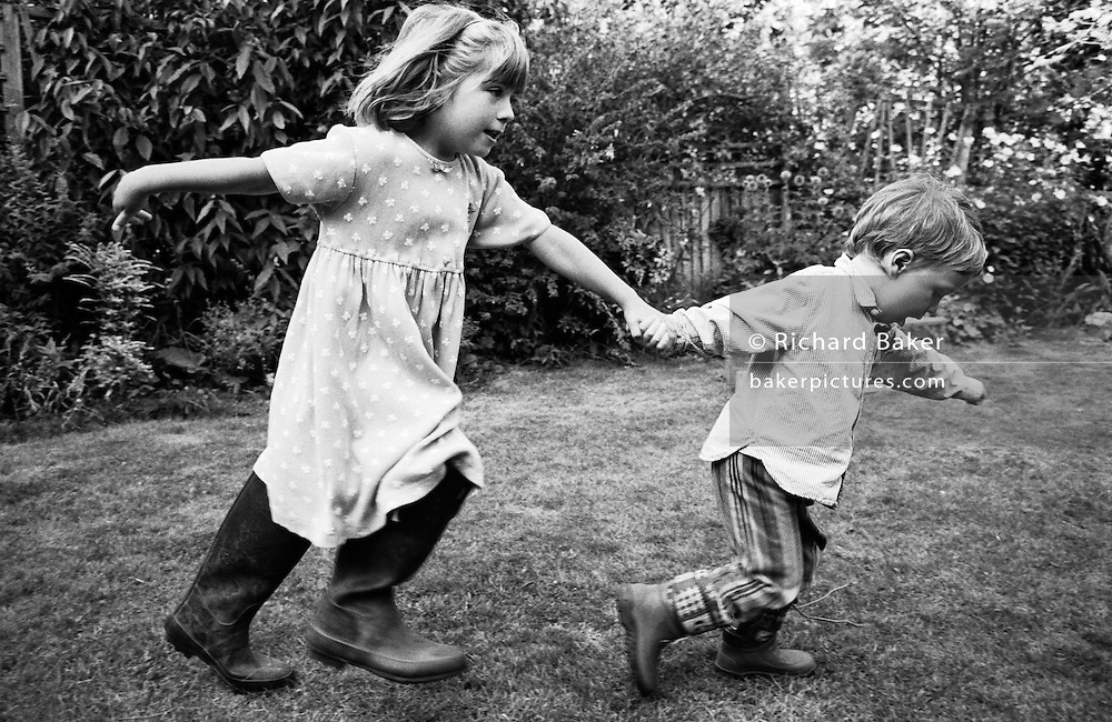 "A brother and sister run through the back garden of their South London home. We see the younger sibling - a boy of three leading his big sister by the hand in some sort of follow-my-leader game. He pulls hard to tow the girl along who wears Wellington boots that are too large for her and they both hold out their arms for stability. From a personal documentary project entitled ""Next of Kin"" about the photographer's two children's early years spent in parallel universes. Model released."