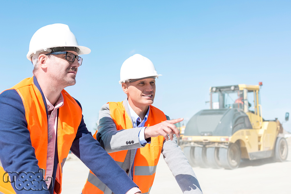 Supervisor explaining plan to colleague at construction site against clear sky
