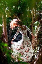 Woman in Floral Dress Tossing Hair amongst Fern Trees in Forest