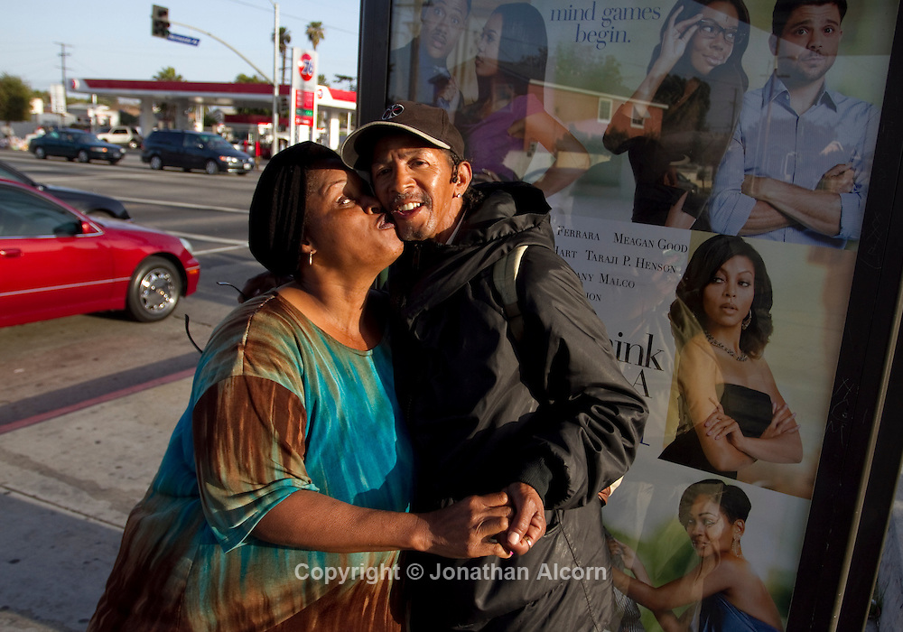 Denise Lemmons kisses Wellington Warner at a bus stop located at the intersection of Florence and Normandie in Los Angeles, California. This April 29 will be the 20 year anniversary of the flashpoint of the Los Angeles Riots in the area of Florence and Normandie in South Los Angeles. ©Jonathan Alcorn/JTA