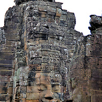 Faces on Prasats at Bayon in Angkor Archaeological Park, Cambodia<br /> The experience of seeing over 200 nearly identical stone faces carved into towers is exhilarating. Most of the prasats have four faces looking in opposite directions. The tallest one measures over eight feet. This display on the highest level of Bayon is often tarnished by throngs of tourists crowded onto a small terrace. Consequently, the best way to enjoy this unique excursion is to arrive early.
