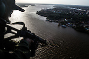 A Aerial Tactical Group soldier patrols one of the dozens of canals amid river islands just in front of Santana port in Amapa, Brazil, Thursday, Oct. 27, 2016.  With a huge estuary to look the police group forces are called depending on the kind of occurrence goes on but a structured force in the shape of Brazilian road feds is yet to be created.  (Dado Galdieri for The New York Times)