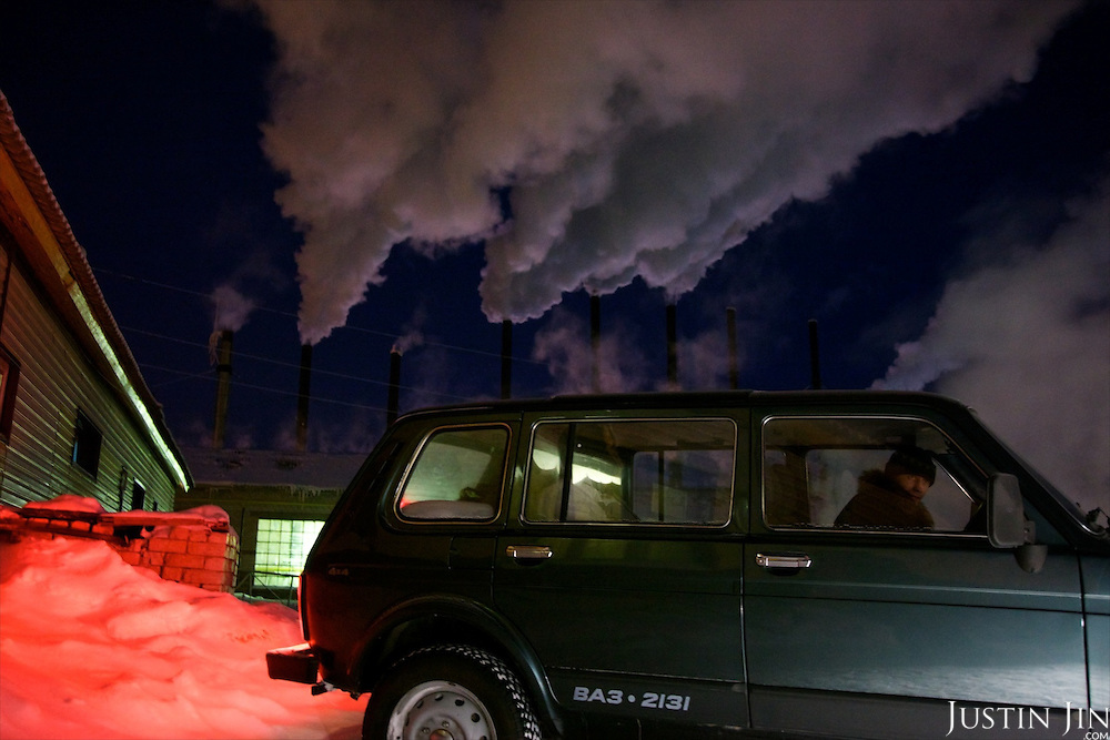 A water-heating plant emits steam in Arctic Russia. Supporting an Arctic city is costly because of its cold, distance and isolation.
