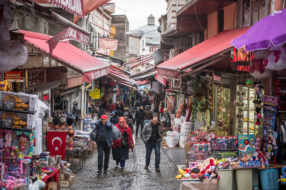 People walk up hill on a narrow street where shops and stalls for outdoor market line either side of the tight space, Istanbul, Turkey