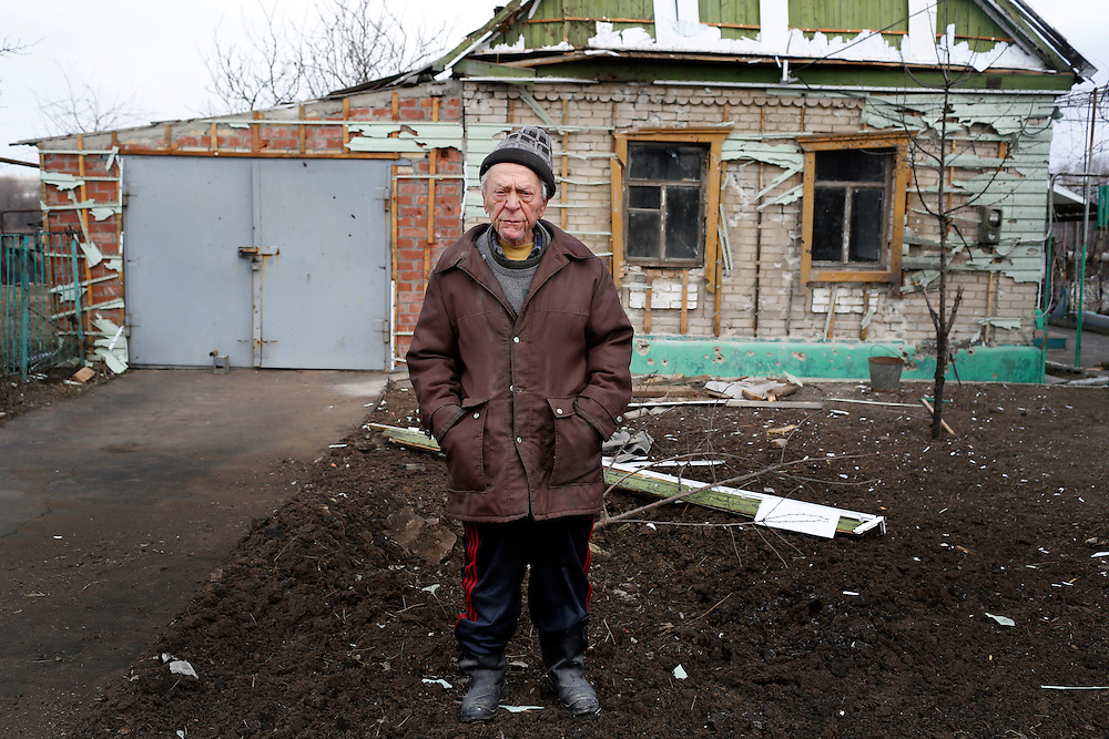 Ivan Nahorski poses for a portrait in the front yard of his damaged home on February 7, 2015 in Luganske, Ukraine. Six shells exploded within 300 meters of each other in this small village near Debaltseve.