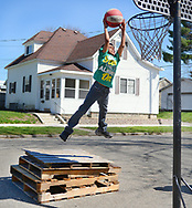"PALLET POWERED --- ""I watch the NBA and I watch Jalen Adaway then I just do it,"" said Trevon ""Peanut"" Holiday, 10, of Logansport, about his ability to slam dunk the basketball. He got a little extra lift  from a stack of wooden pallets he and his cousin Adrian Piland, 11, dragged onto the side of the street near 17th and High Street Saturday afternoon. Talking about his own dunking skills Piland said, ""I like the adrenaline rush and I like hanging around with my cousin."" J. Kyle Keener 