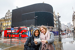 © Licensed to London News Pictures. 16/01/2017. London, UK. Two tourists take picture of themselves with the iconic electronic billboards of Piccadilly Circus, which have been switched off for renovations for the longest period of time since the Blitz, as part of a plan to remove the six illuminated advertising boards which overlook the tourist hotspot and replace them with one ultra-high definition curved screen and will be unveiled in the autumn. Photo credit: Tolga Akmen/LNP