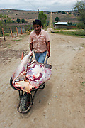 A MAN IS COMING OUT FROM THE SLAUGHTERHOUSE WITH THE MEAT READY TO BE SELL IN THE LOCAL MARKET.