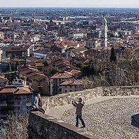 Bergamo, Italy - A man takes a picture to two tourists sitting on the ancient walls of Uppoer Bergamo (Bergamo Alta). Below, Lower Bergamo (Bergamo Bassa) with the Campanile di S. Alessandro in Colonna