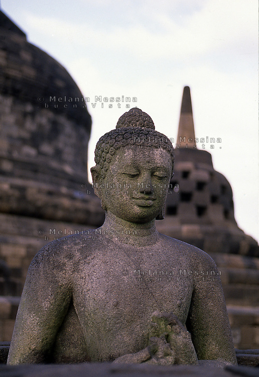 Central Java, Indonesia: detail of The Borobudur temple, Buddha statue surrounded by stupas.<br />