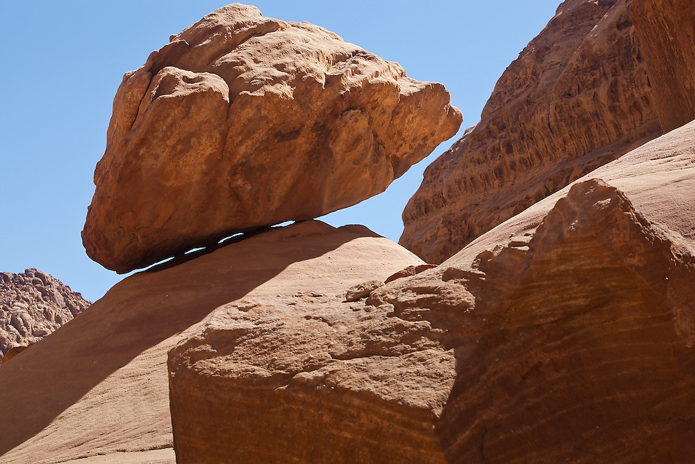 A boulder at the angle of repose in a small sandstone canyon in Wadi Rum, Jordan.