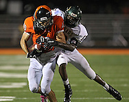 Prairie's Mitchell Christensen (40) is pulled down by Kennedy's Famiek Cook (12) on a run during their game at John Wall Memorial Stadium at Prairie High School in Cedar Rapids on Friday, September 6, 2013.