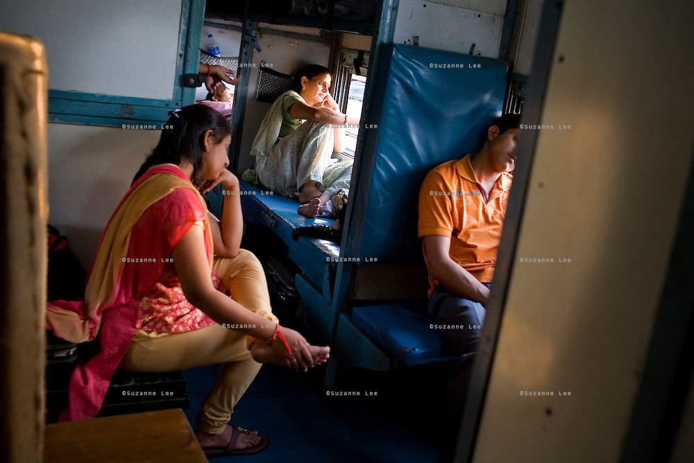Nitika Jindal (right) a culinary student from Jakhal, Punjab, looks out the door of the train in the non-airconditioned sleeper class...Train passengers on the Himsagar Express 6318 going from Jammu Tawi station to Kanyakumari on 7th July 2009..  .6318 / Himsagar Express, India's longest single train journey, spanning over 3720 kms, going from the mountains (Hima) to the seas (Sagar), from Jammu and Kashmir state in the Indian Himalayas to Kanyakumari, the southern-most tip of India..Photo by Suzanne Lee / for The National.