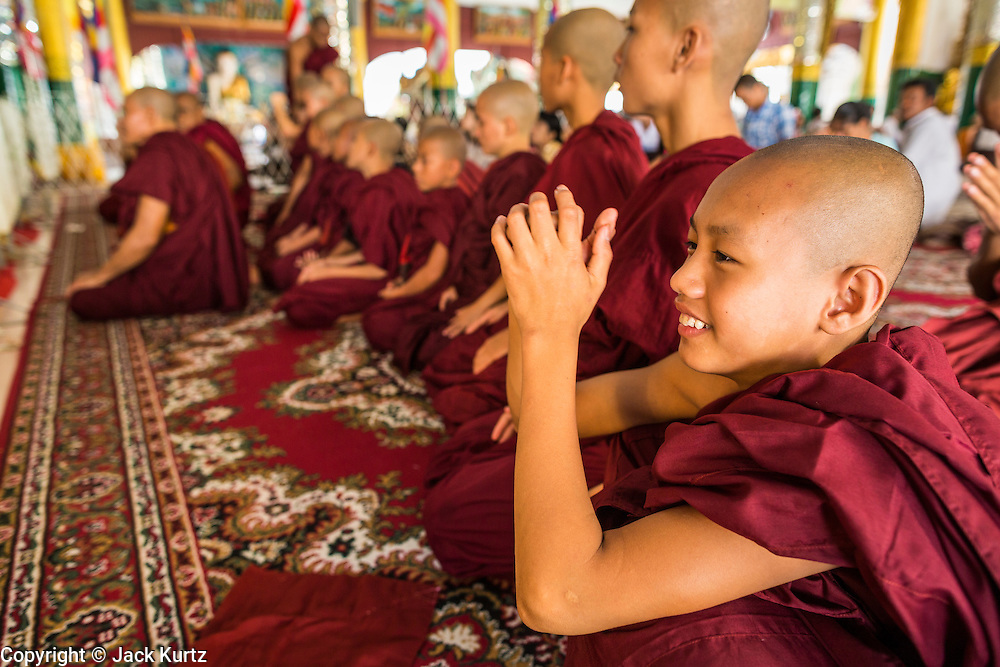 15 JUNE 2013 - YANGON, MYANMAR:  Buddhist novices pray at Shwedagon Pagoda. Shwedagon Pagoda is officially known as Shwedagon Zedi Daw and is also called the Great Dagon Pagoda or the Golden Pagoda. It is a 99 meter (325 ft) tall pagoda and stupa located in Yangon, Burma. The pagoda lies to the west of on Singuttara Hill, and dominates the skyline of the city. It is the most sacred Buddhist pagoda in Myanmar and contains relics of the past four Buddhas enshrined: the staff of Kakusandha, the water filter of Koṇāgamana, a piece of the robe of Kassapa and eight strands of hair from Gautama, the historical Buddha. Burmese believe the pagoda was established as early ca 540BC, but archaeological suggests it was built between the 6th and 10th centuries. The pagoda has been renovated numerous times through the centuries. Millions of Burmese and tens of thousands of tourists visit the pagoda every year, which is the most visited site in Yangon. PHOTO BY JACK KURTZ