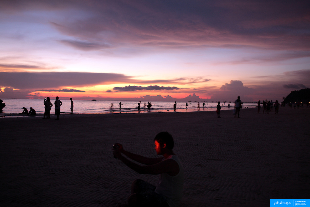 An Asian tourist takes a self portrait during sunset at White Beach,  Boracay Island, the Philippines on October 4, 2008, Photo Tim Clayton.....Asian tourists at White Beach, Boracay Island, the Philippines...The 4 km stretch of White beach on Boracay Island, the Philippines has been honoured as the best leisure destination in Asia beating popular destinations such as Bali in Indonesia and Sanya in China in a recent survey conducted by an International Travel Magazine with 2.2 million viewers taking part in the online poll...Last year, close to 600,000 visitors visited Boracay with South Korea providing 128,909 visitors followed by Japan, 35,294, USA, 13,362 and China 12,720...A popular destination for South Korean divers and honeymooners, Boracay is now attracting crowds of tourists from mainland China who are arriving in ever increasing numbers. In Asia, China has already overtaken Japan to become the largest source of outland travelers...Boracay's main attraction is 4 km of pristine powder fine white sand and the crystal clear azure water making it a popular destination for Scuba diving with nearly 20 dive centers along White beach. The stretch of shady palm trees separate the beach from the line of hotels, restaurants, bars and cafes. It's pulsating nightlife with the friendly locals make it increasingly popular with the asian tourists...The Boracay sailing boats provide endless tourist entertainment, particularly during the amazing sunsets when the silhouetted sails provide picture postcard scenes along the shoreline...Boracay Island is situated an hours flight from Manila and it's close proximity to South Korea, China, Taiwan and Japan means it is a growing destination for Asian tourists... By 2010, the island of Boracay expects to have 1,000,000 visitors.