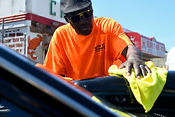 Dave Terrell, 57 works on polishing the exterior of a vehicle as members of the local classic and American muscle car community gathers for a meet on a North Philadelphia, on Sunday.