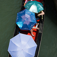 A group of tourists tries to find shelters under umbrella while on a Gondola Tour on the day the Italian Government and Heath Ministry has issued several warning for the current heath wave