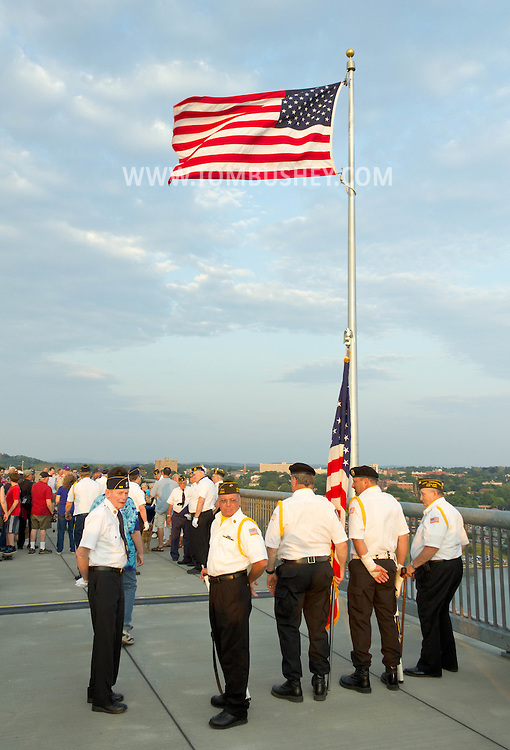 Highland, New York - People walk along the Walkway over the Hudson on May 27, 2012. A Memorial Day ceremony was held by the American flag at the center of the walkway at dusk.