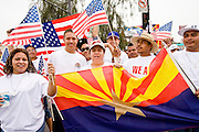 10 APRIL 2006 - PHOENIX, AZ: Immigrants carry US and Arizona flags during an immigration march in Phoenix, AZ. More than 125,000 people participated in a march for immigrants's rights in Phoenix Monday. The march was a part of a national day of action on behalf of undocumented immigrants. There were more than 100 such demonstrations across the US Monday.  Photo by Jack Kurtz